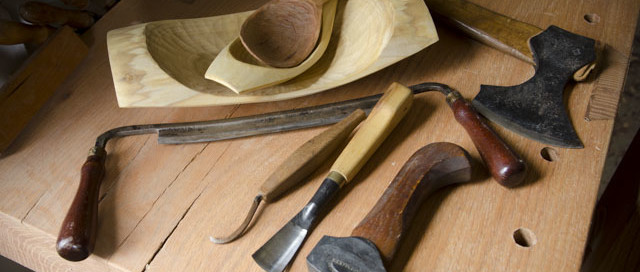 Green woodworking tools for carving bowls and spoons, sitting on a woodworking workbench, including a bowl adze, carving gouge, hook knife, axe, and drawknife