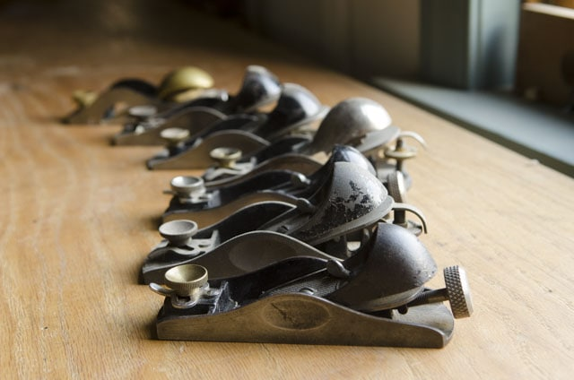 Antique stanley block planes sitting on a woodworking workbench in a row