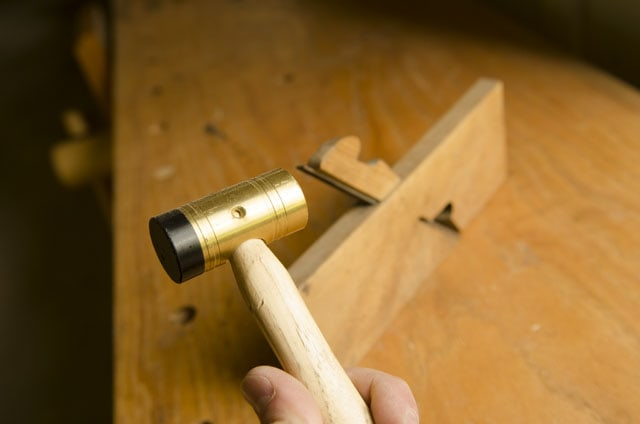 Grace USA brass mallet with a rabbet plane in the background sitting on a woodworking workbench