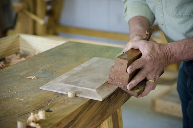 Man's hands using a wooden moving fillister plane to cut a panel for frame and panel door