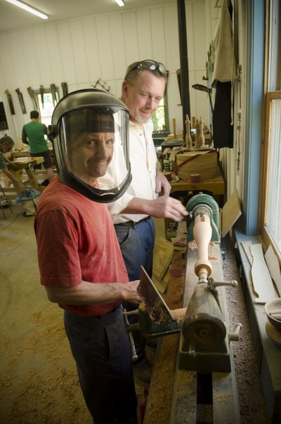 Woodworking student turning a table spindle at the Wood and Shop Traditional Woodworking School with a face mask on under the watch of instructor Will Myers