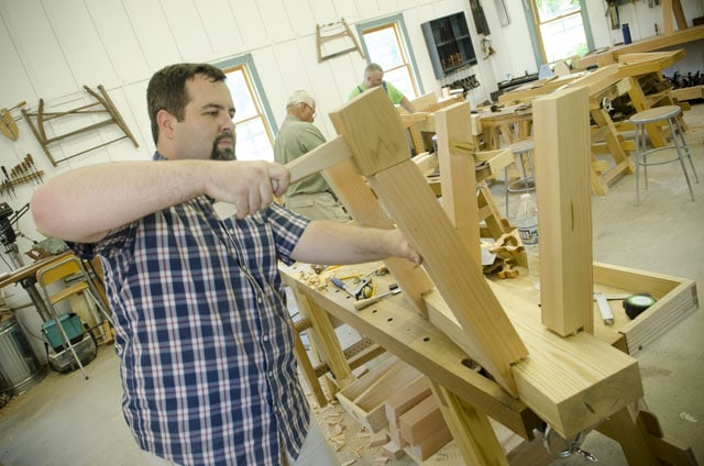 woodworking student using a joiner's mallet to build a timber framing saw benches for woodworking hand saw