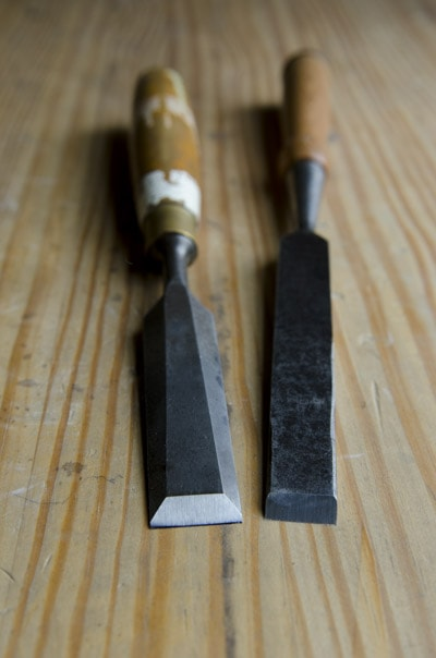 Two antique wood chisels sitting on a woodworking workbench: a bevel edge bench chisel and a non beveled bench chisel