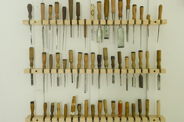 A whole wall of antique chisels on a rack in the Wood and Shop Traditional Woodworking school