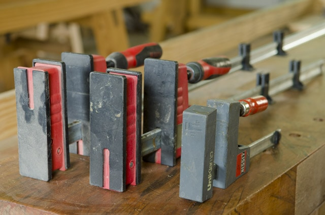 Bessey Parallell bar woodworking clamps sitting on a woodworking workbench