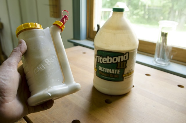 Glu Bot glue bottle being held with a bottle of Titebond 3 wood glue in the background on a woodworking workbench