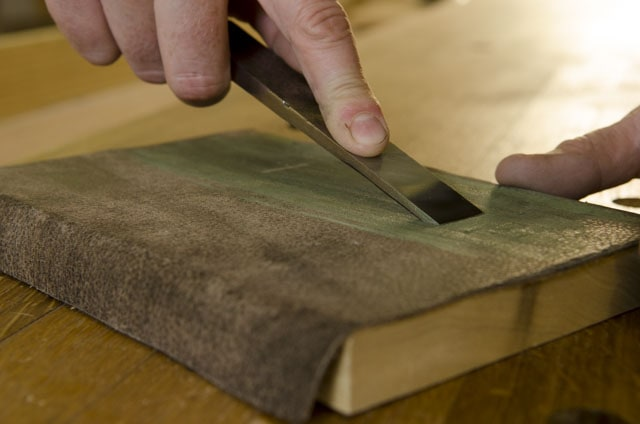 Stropping a woodworking wood chisel on a leather stop