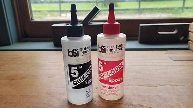Two bottles of Quick-Cure 5 minute epoxy sitting on a woodworking workbench