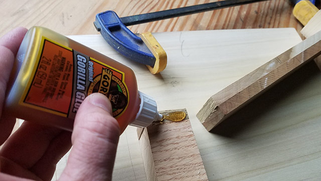 Gorilla glue 2 oz bottle polyurethane glue gluing a broken piece of wood with a blue clamp in the background