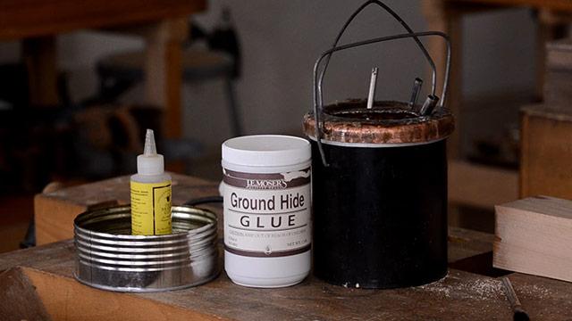Animal hide glue bottle and liquid hide glue next to a glue pot