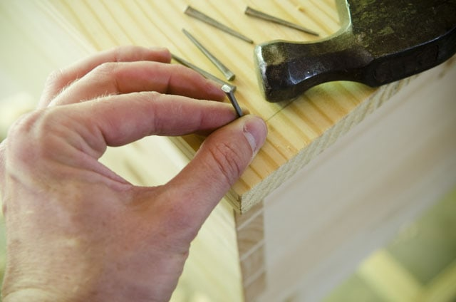 Woodworker holding a historical style cut nail for hammering a wooden desk top on