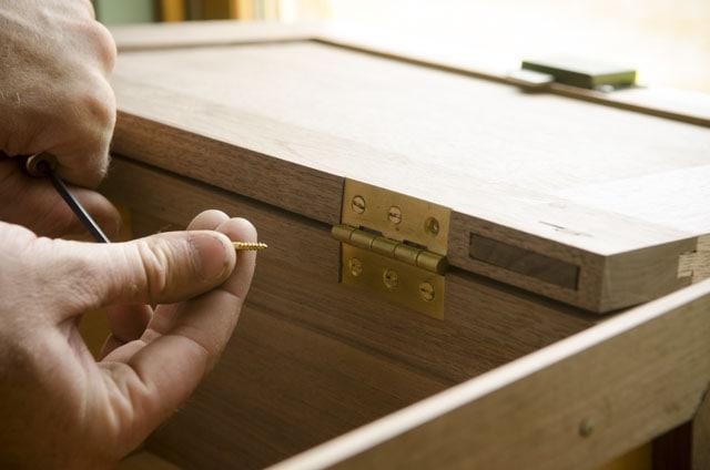 Woodworker adding brass screws into a cupboard door brass hinge with clocked screws