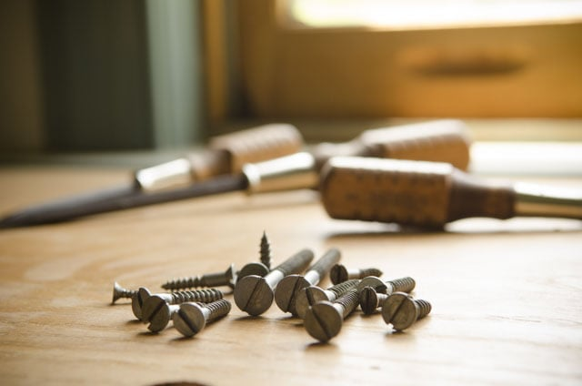Grace brand screwdrivers sitting on a woodworking workbench with historical style slotted screws