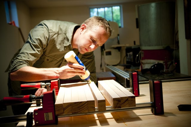 Woodworker spreading glue on a butcher block cutting board with woodworking clamps