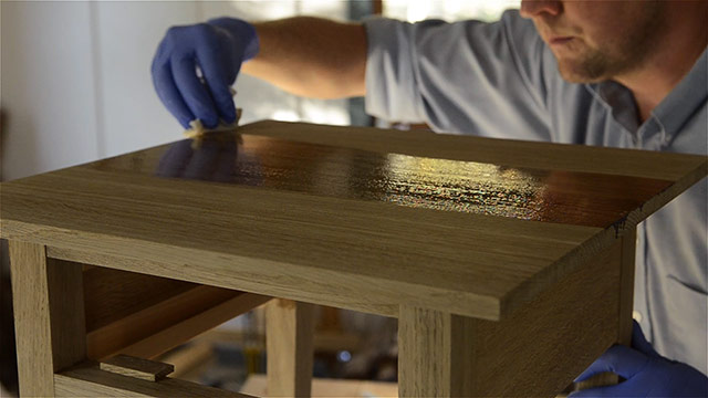Joshua Farnsworth applying wood finish to an oak table top in his woodworking workshop