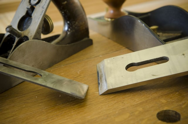 Bevel up and bevel down hand plane irons sitting next to two hand planes sitting on a woodworking workbench Stanley number 3 smoothing plane and Lie-Nielsen number 62 low angle jack plane