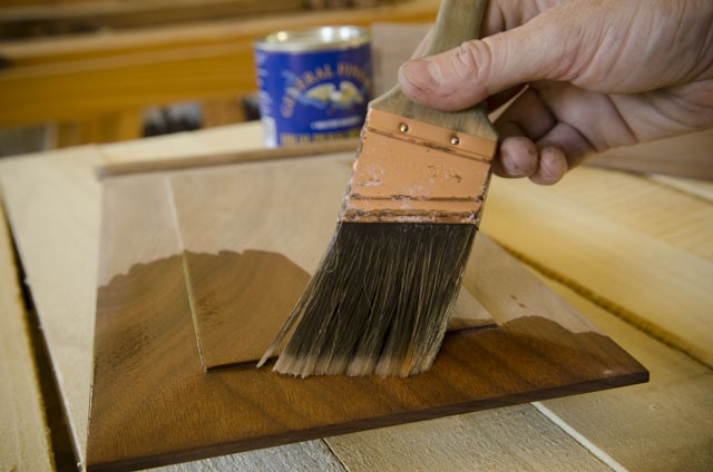 Applying wood finish to a walnut panel with a purdy paint brush with a can of water based finish in the background by General Finishes