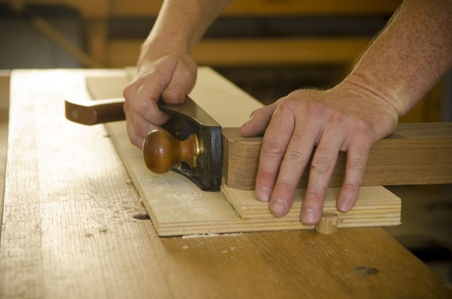 Woodworker Using A Shooting Board With A Lie-Nielsen Number 62 Low Angle Jack Plane To Shoot The End Grain Of A Board On A Wooden Workbench
