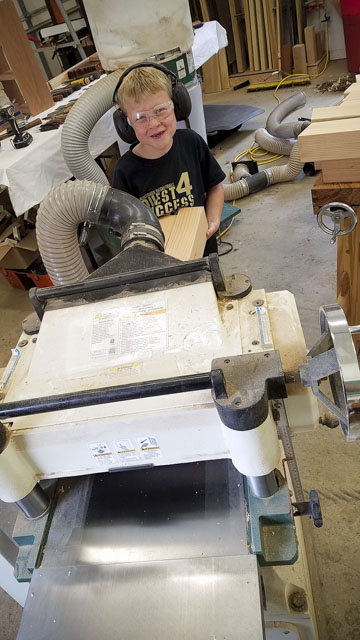 Boy helping with milling wood on a Grizzly thickness planer