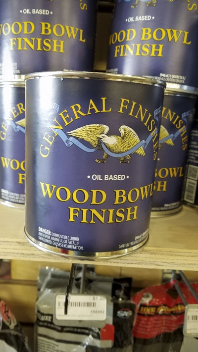 Quart cans of General Finishes oil based wood bowl finish sitting on a shelf in a woodworking store