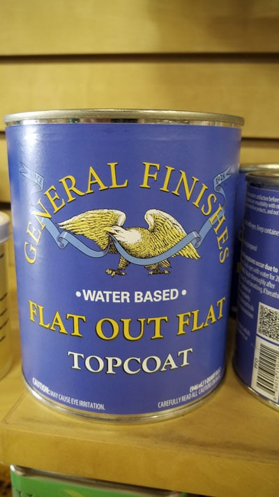 Gallon can of General finishes water based flat out flat topcoat wood finish sitting on a shelf in a woodworking store