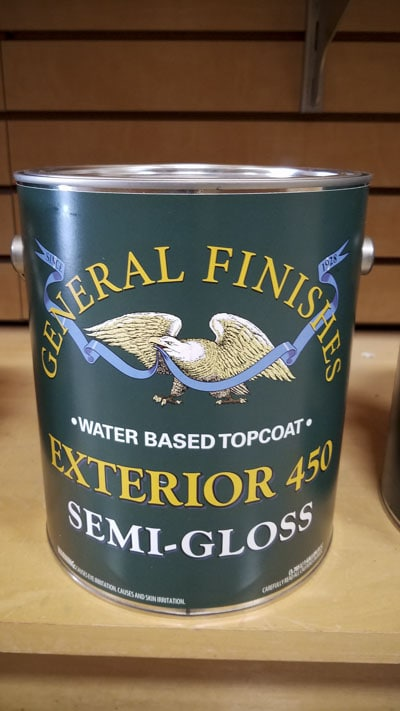 Gallon can of General finishes water based topcoat exterior 450 semi-gloss sitting on a shelf in a woodworking store