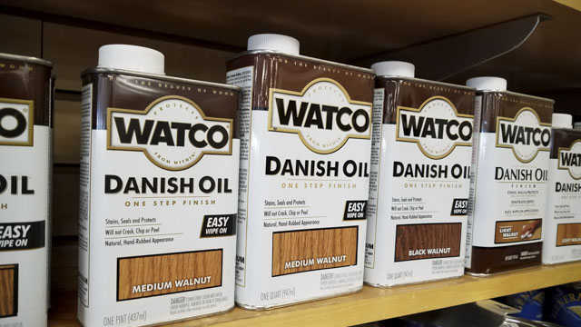 Cans of Watco Danish Oil wood finish sitting on a shelf in a woodworking store