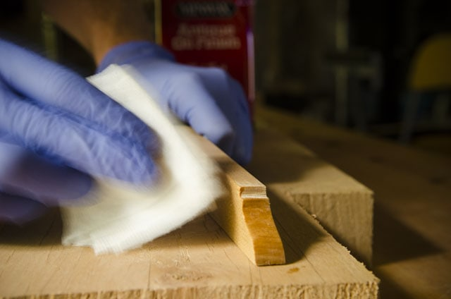 Woodworker applying antique oil finish to a wooden straight edge for woodworking