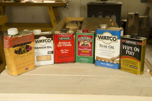 A row of woodworking varnish cans lined up including waterlox, danish oil, tung oil, teak oil, and wipe-on polyurethane