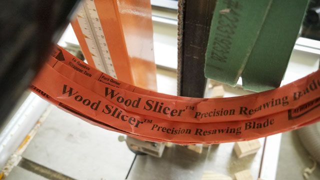 1/2 inch wood slicer precision resawing blade in orange paper packaging with a bandsaw in the background