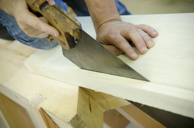 woodworker ripping a board with an antique disston hand saw