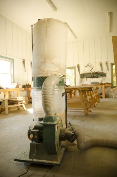 Grizzly G1028Z2 1-1/2 HP Dust Collector in a woodworking workshop with Moravian Workbenches in the background