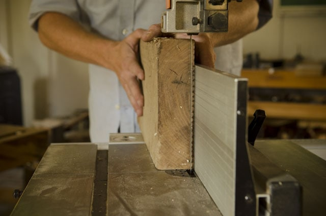 Woodworker resawing a thick walnut board on a bandsaw with a resaw fence