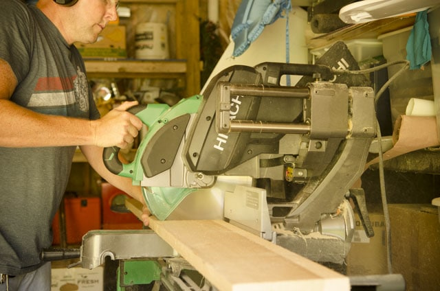 Joshua Farnsworth cutting a board with a Hitachi power miter saw