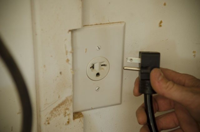 220 volt electrical outlet with woodworker about to plug in a power jointer