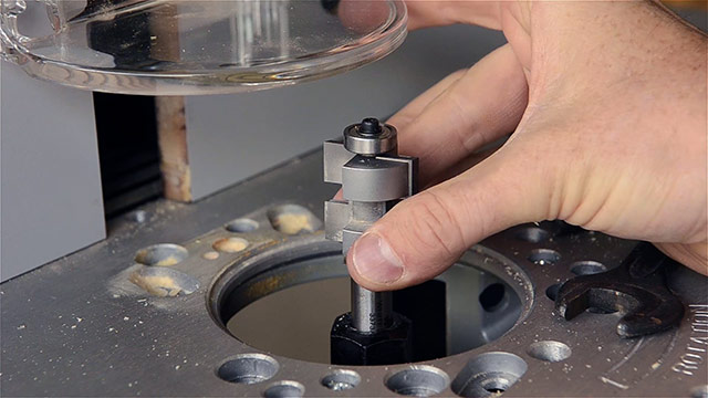 woodworker inserting a router tongue bit in a router collet for cutting a tongue & groove joint