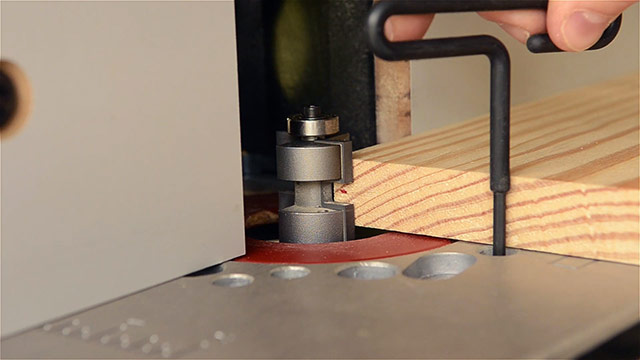 woodworker adjusting the height of a router tongue bit for cutting a tongue & groove joint