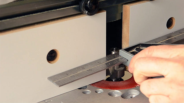 Woodworker aligning a router bit bearing with a router table fence using a combination square