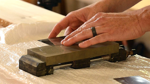 card scraper getting polished on a 1,000 grit norton water stone