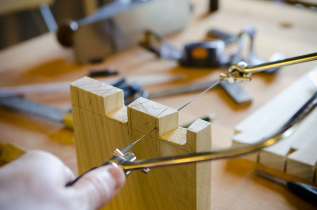 Cutting out the waste of a dovetail joint with a coping saw on a woodworking workbench