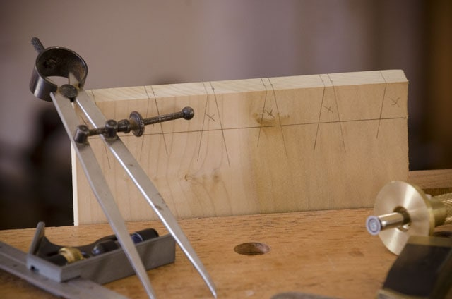 Dovetail tail board with dividers, combination square, marking gauge, and pencil in the foreground
