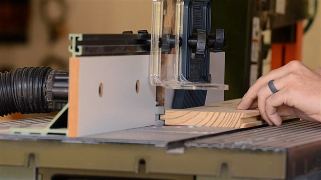 A woodworker making a tongue & groove joint on a router table