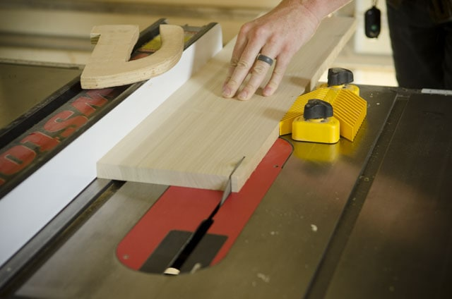 Joshua Farnsworth pushing a poplar board across a SawStop table saw with a wooden push stick next to him and a yellow feather board