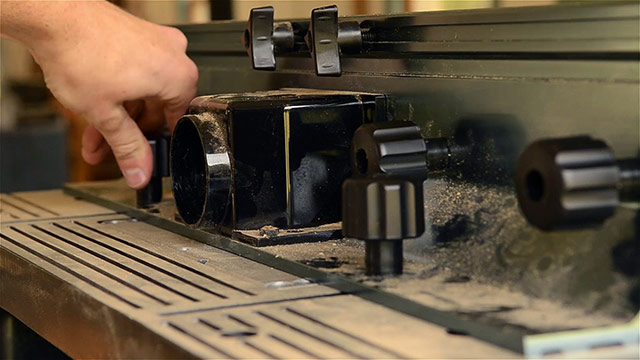 woodworker tightening the fence knob on a router table