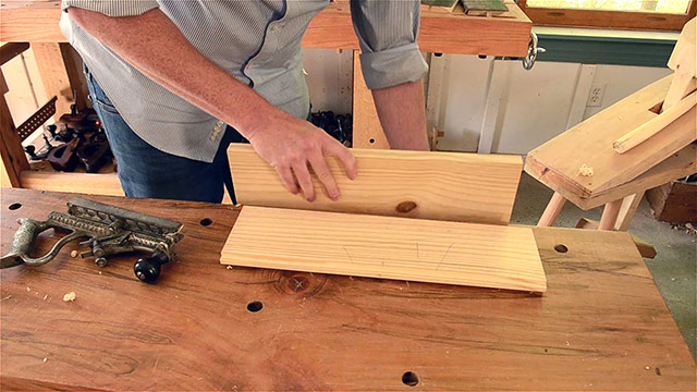 Woodworker placing a groove board in the workbench vise in preparation for handplaning the groove of the tongue & groove joint