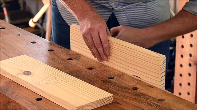 Woodworker placing a tongue board in the workbench vise in preparation for handplaning the tongue of the tongue & groove joint