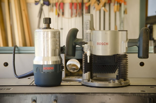 Bosch router motor sitting on a router table next to a plunge router base