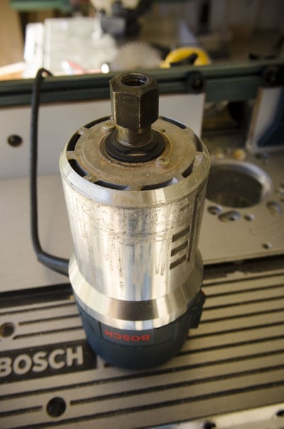 A Bosch router motor sitting upside down on a router table