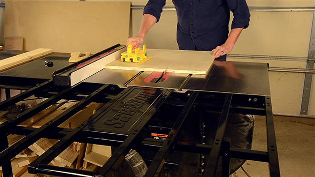 SawStop folding outfeed table being used to cut a sheet of plywood on a table saw