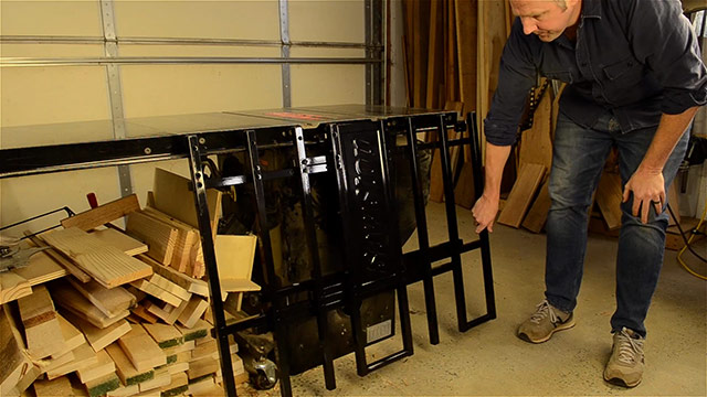 Joshua Farnsworth folding down a newly assembled SawStop folding outfeed table on his SawStop cabinet saw